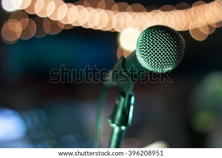 Close up of microphone on stage background at outdoor night party - stock photo