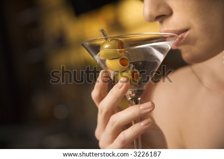 Close up of mid adult Caucasian woman drinking a martini with three olives. - stock photo