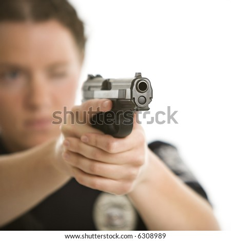 Close up of mid adult female Caucasian law enforcement officer aiming gun at viewer with one eye closed. - stock photo