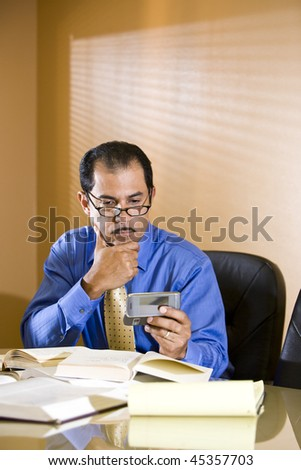 Close-up of middle-aged Hispanic businessman staring at text message on mobile phone - stock photo