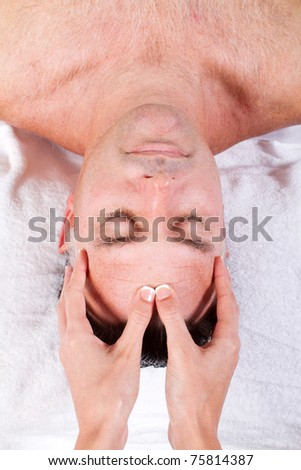 Close up of middle aged man receiving facial massage from a woman - stock photo
