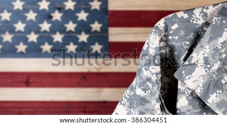 Close up of military uniform with painted rustic boards of USA flag in background.
