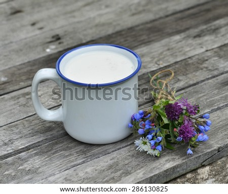 Close up of milk in cup with flower bunch on wooden planks, summer still life - stock photo