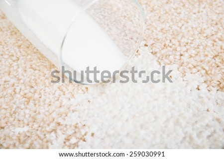 Close-up Of Milk Spilled From Glass On Carpet - stock photo