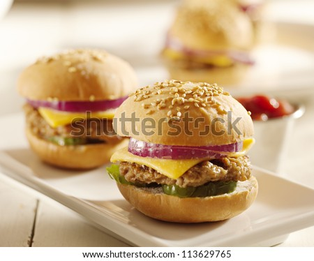 close up of mini burgers with cheese, onion and pickle. - stock photo