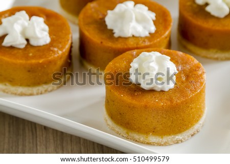 Close up of mini round pumpkin pies topped with whipped cream sitting on white square plate