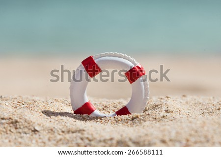 Close-up Of Miniature Lifebuoy On Sandy Beach - stock photo