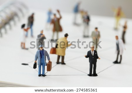 close up of miniature people with social network diagram on open notebook on wooden desk as social media concept
