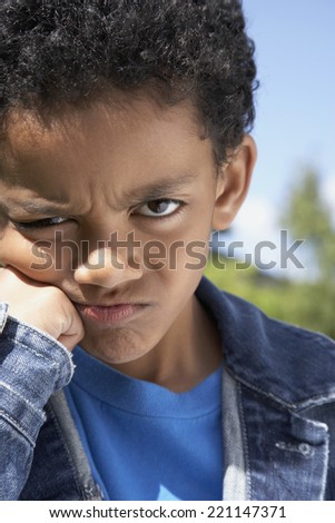 Close up of Mixed Race boy frowning - stock photo