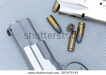 Close up of 9 mm. bullets with 9 mm. handgun in background - stock photo