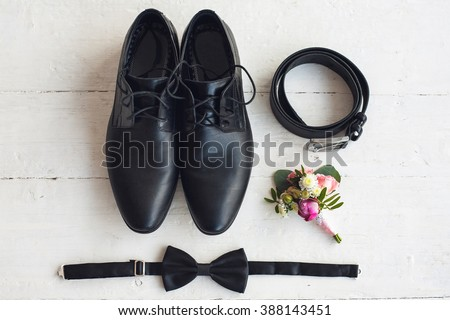 Close up of modern man accessories. Black bowtie, leather shoes, belt and flower boutonniere on white wood rustic background. Set for formal style of wearing isolated on white background. - stock photo