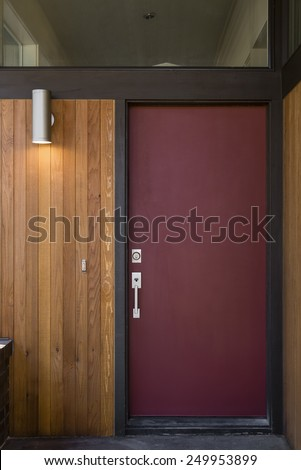 Close Up of Modern Red Front Door with Large Overhead Window and Natural Wood Panel Exterior - stock photo