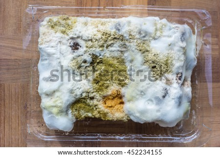 Close up of mold growing on cake in green and white spores - stock photo