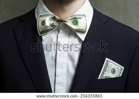 Close up of money in male suit pocket. Bow-tie in the form of bills.