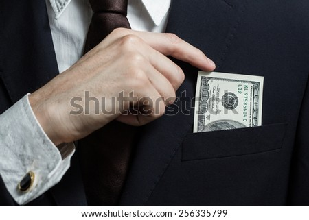 Close up of money in male suit pocket. Puts money in your pocket - stock photo