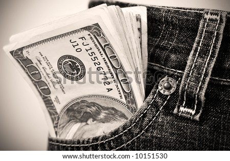 Close-up of money sticking out from pocket. Sepia tone. Shallow DOF. - stock photo