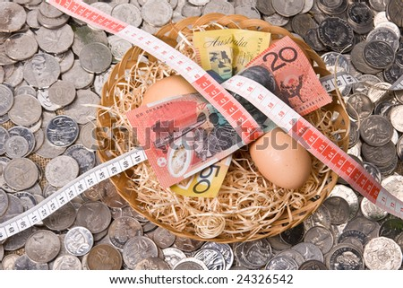 close up of money with eggs in nest with tape measure - australian currency notes and coins and tape measure - stock photo