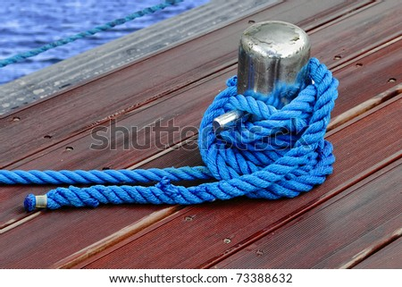Close-up of mooring bollard with blue rope in marina - stock photo