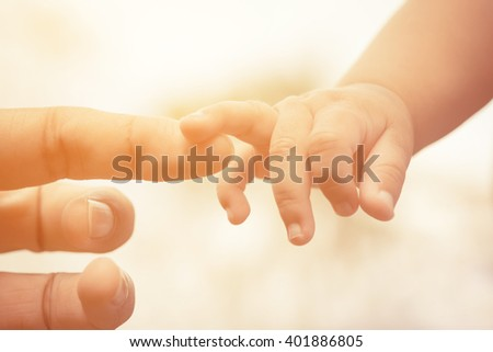 Close-up of mother and baby's hands and color tone effect - stock photo