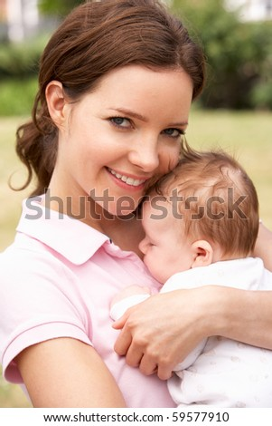 Close Up Of Mother Cuddling Newborn Baby Boy Outdoors At Home - stock photo