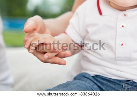 Close-up of mother holding child's hand - stock photo