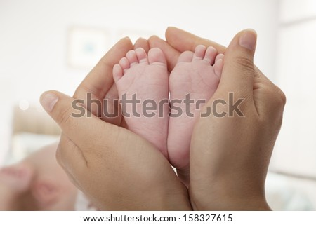 Close-up of mother holding her baby's feet