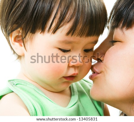 Close-up of mother kissing her small daughter lovingly over white background - stock photo