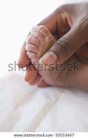 close up of mother's hand holding baby's foot - stock photo
