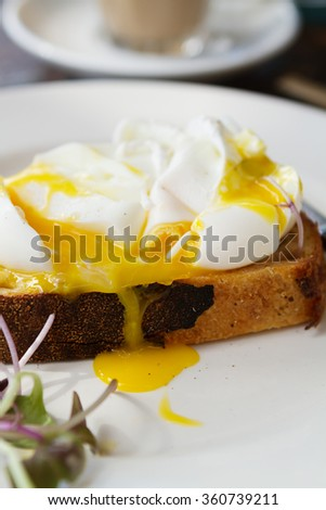 Close up of mouth watering poached egg yolk dripping down toast - stock photo