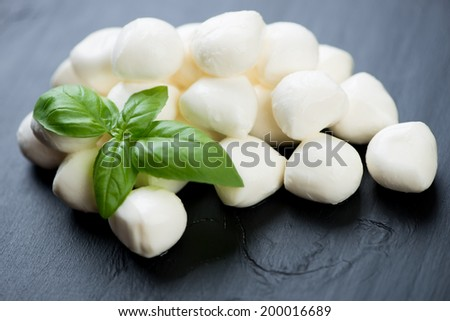 Close-up of mozzarella balls with green basil, horizontal shot