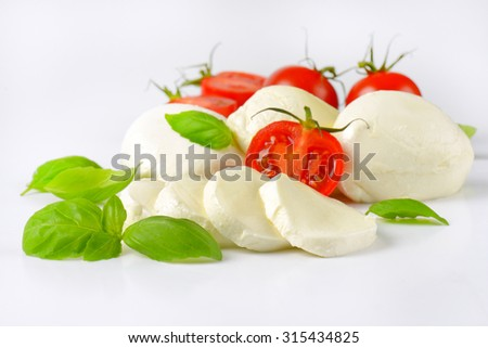 close up of mozzarella, cherry tomatoes and fresh basil - ingredients for caprese salad - stock photo