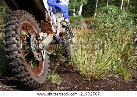 Close-up of muddy rear wheel and engine of dirt bike, details - stock photo