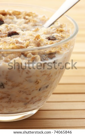 Close-up of muesli with milk in glass bowl and spoon on wooden surface. - stock photo