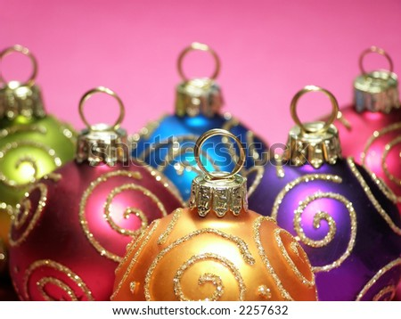 Close-up of multi colored Christmas baubles in a row with swirl decoration in gold