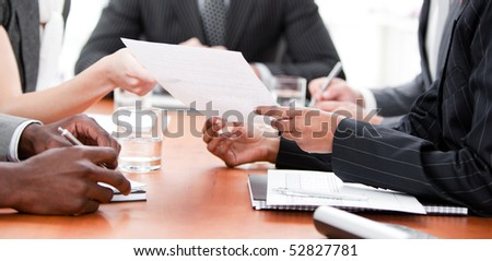 Close-up of multi-ethnic business people working in a meeting - stock photo