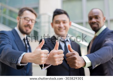 Close-up of multi ethnic business team holding their thumbs up. Three  men hands showing thumbs up against the backdrop of the city. The one man is European, other is Chinese and African-American.  - stock photo