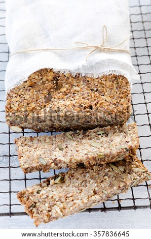 Close up of multi seeded whole wheat bread with nuts, pumpkin, sunflower, sesame, flax seeds and almonds - stock photo