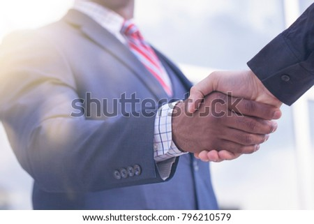 Close-up of multiethnic business partners shaking hands for greeting or partnership