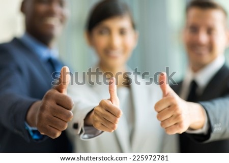 close up of multiracial business team giving thumbs up - stock photo