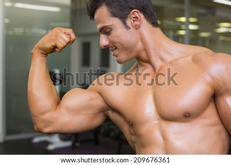 Close-up of muscular man flexing muscles in gym - stock photo