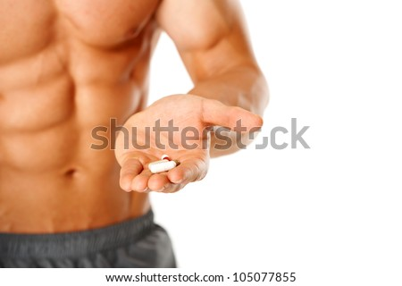 Close up of muscular man torso with hand full of pills on white - stock photo