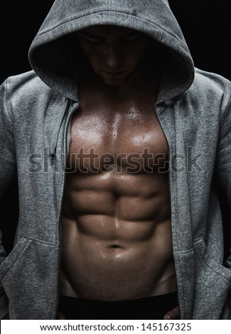 Close up of muscular sports man after weights training over black background - stock photo