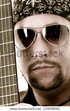Close-up of musician and his guitar. face and strings color processed - stock photo