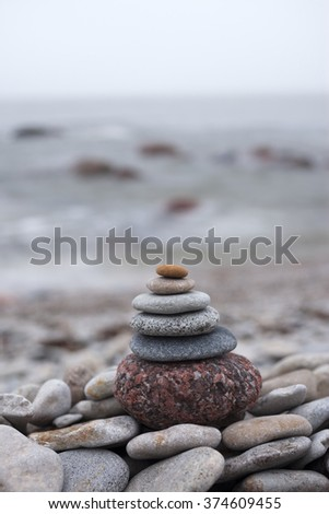 Close up of natural sea-washed stones piled on top of each other at seaside. Very shallow DOF.  - stock photo