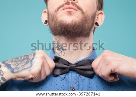 Close up of neck of cool man adjusting a bow with seriousness. He is standing and raising his chin up - stock photo