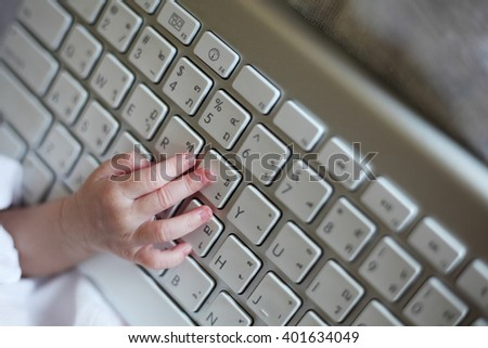 Close-up of New Born Baby's Hand Using Keyboard