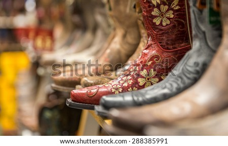Close-up of new cowboy boots on shelf in a store - stock photo