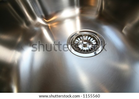 Close-up of new stainless steel kitchen sink __ focus on front side of strainer - stock photo