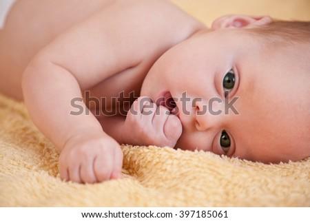 Close up of newborn baby on yellow background - stock photo