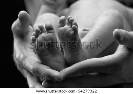 Close up of newborn feet and adult hands, conceptual shot of parenthood caring.